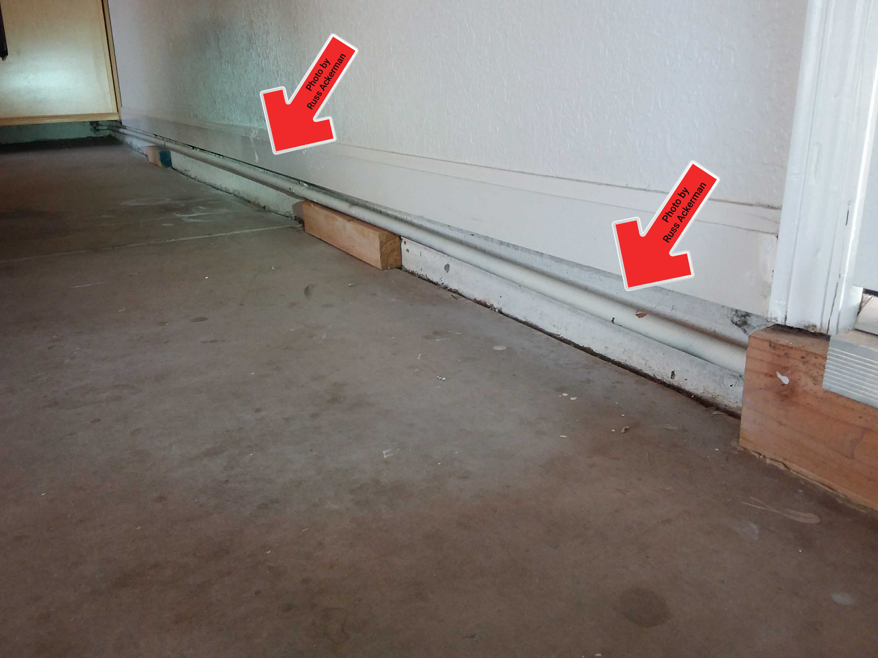 These water supply pipes in the garage are in need of additional support to reduce stress on pipes. Unsecured blocks of wood are not sufficient.
