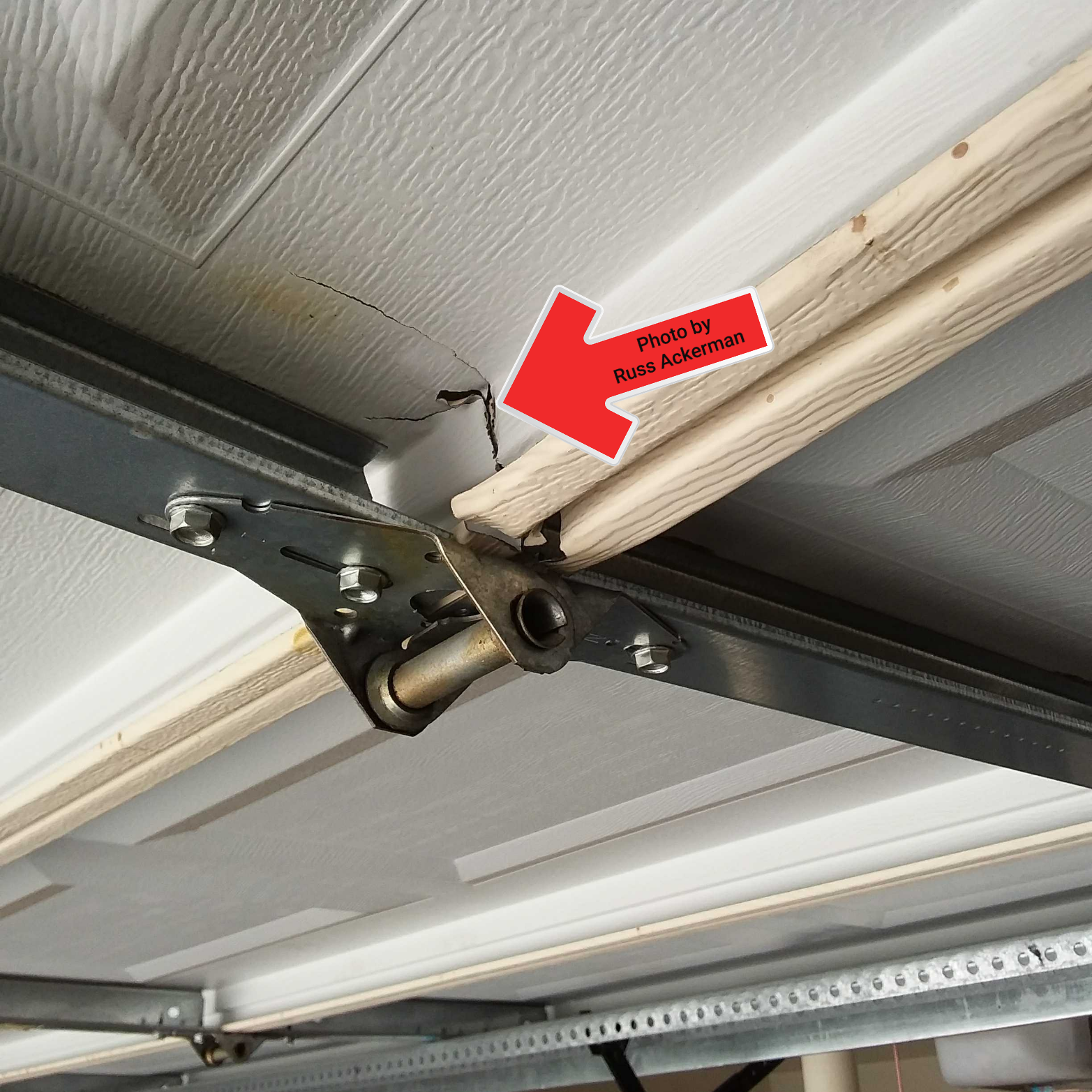This damaged garage door can barely support itself when open and is a potential collapse hazard. Replacement is needed.