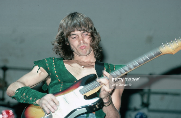 Guitarist Roger Fisher performs with Heart. He is shown waist-up, wearing a green suede shirt and a heart pendant. Photograph, 1977.