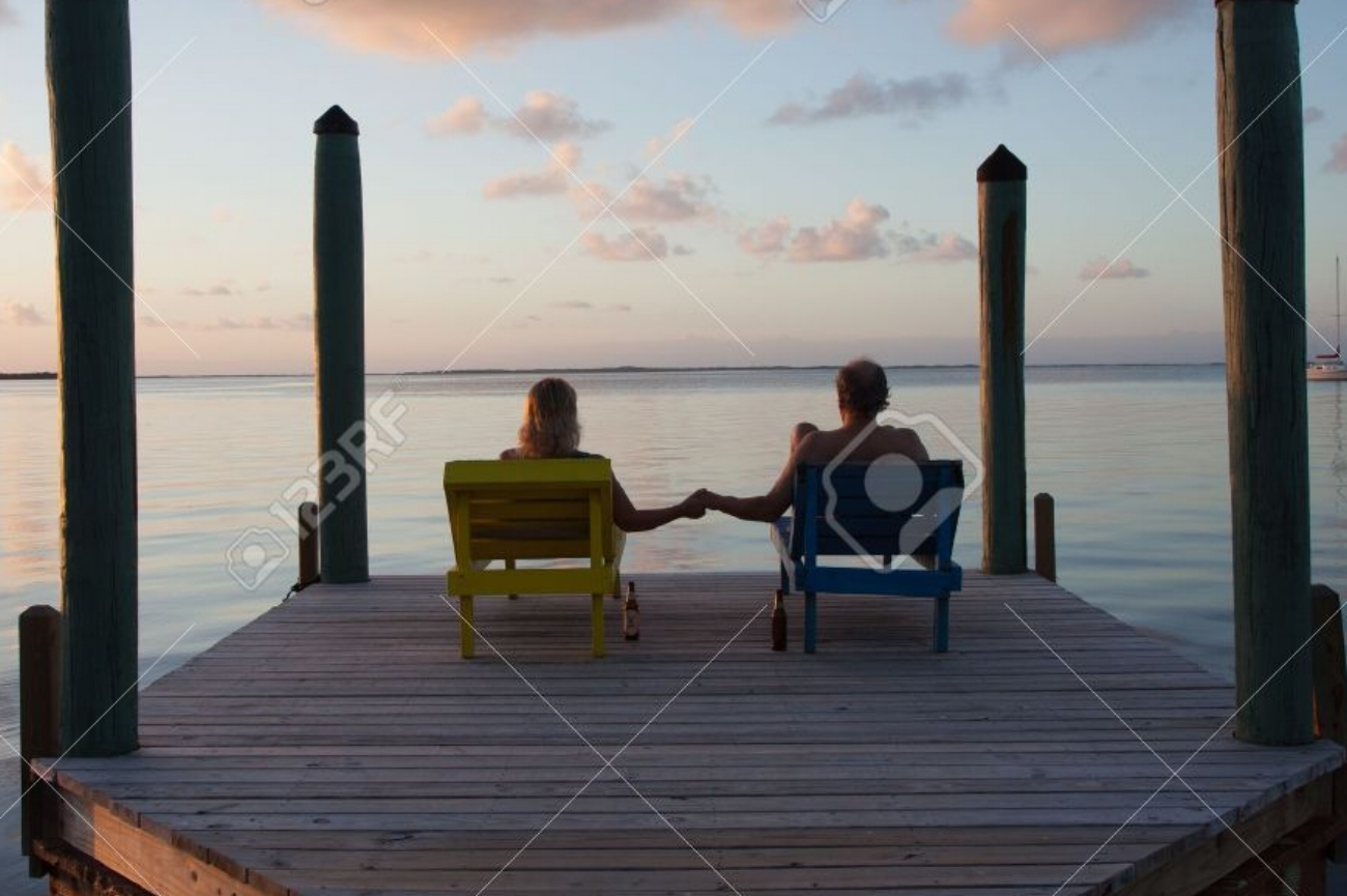 17380003-Couple-sits-on-dock-and-dreams-of-the-future-while-watching-a-beautiful-sunset-Stock-Photo.jpg