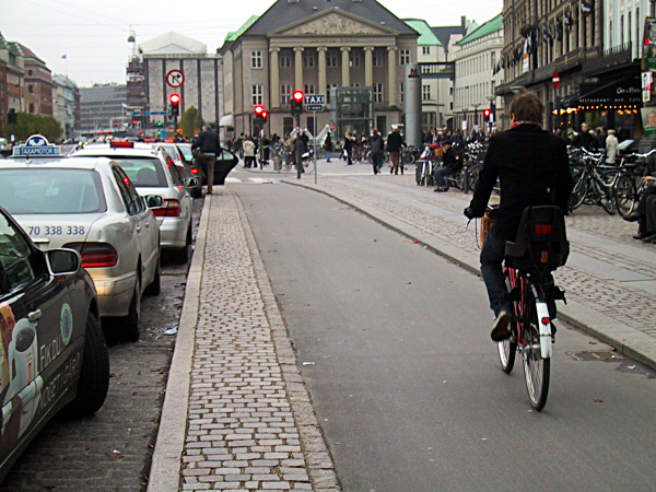 A cycletrack in Copenhagen, Denmark. Notice how everything else on the street is made with cobblestone except the smooth path for bikes? Photo credit: peopleforbikes.org