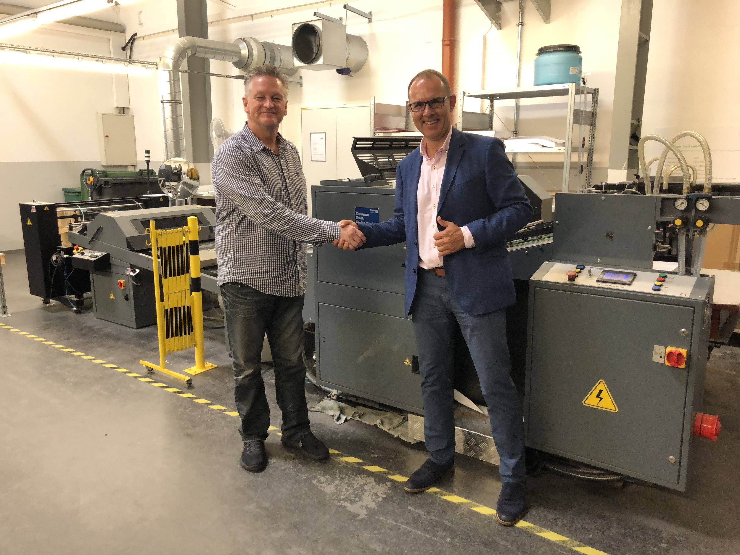 Pictured L to R:  Thomas Hayes, President of Kompac, and Krzysztof Pisera, Business Development Director of Scorpio, standing with a Kwik Finish 32 UV & aqueous coating system.