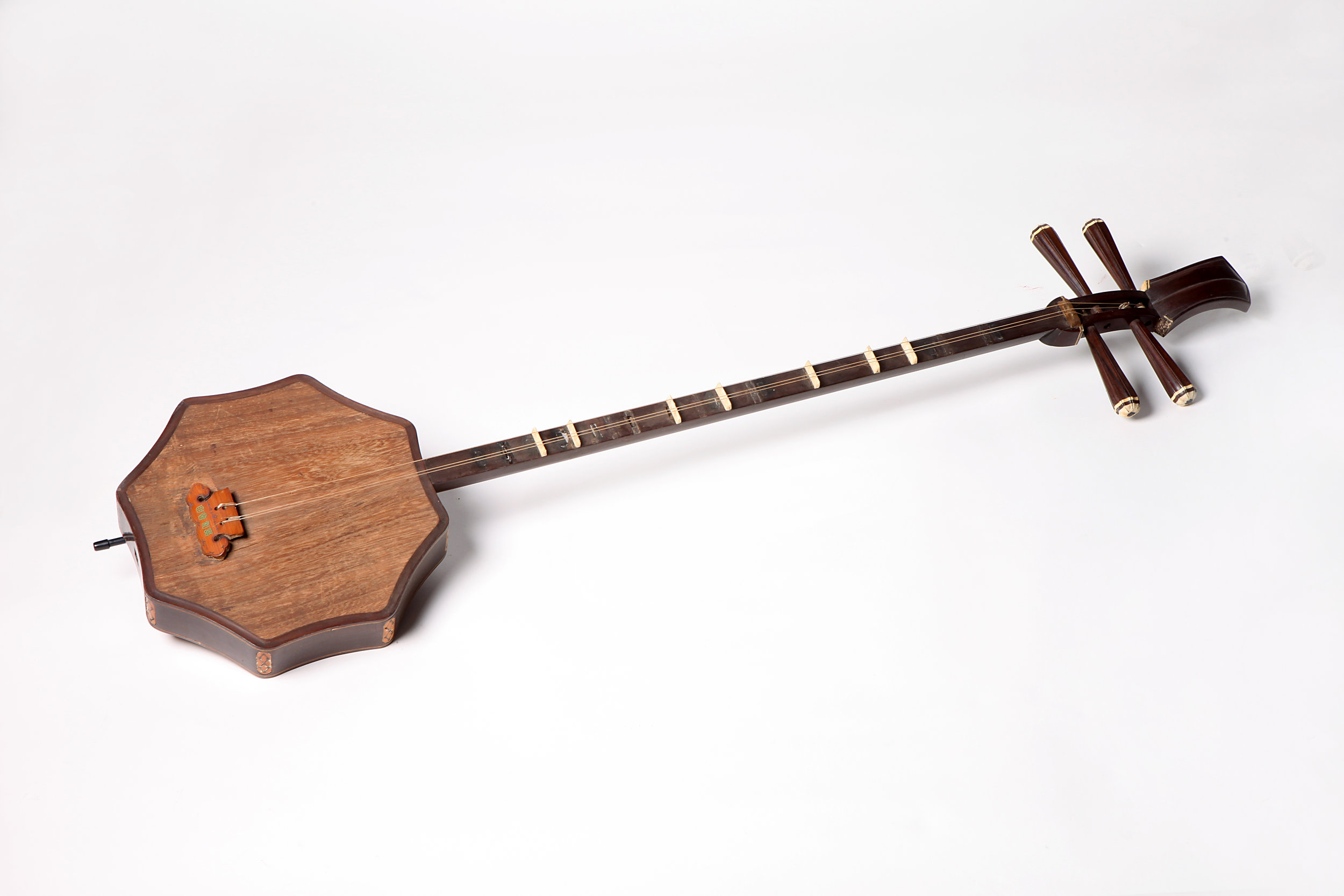 "Shuangqing   is originated from  ruan  (Chinese plucked string instrument) with thinner and longer neck than  ruan . The sound box of  shuangqing  is octagon-shaped with four pegs, four strings and thirteen or fourteen frets. According to  A Sequel to Wenxian Tongkao in Qing Dynasty (qingchao xu wenxian tongkao) , "" shuangqing  is in the  ruan  family and is an alto instrument. It is three  chi  and two  cun  long with an eight- cun  deep peg box. Its sound box is one  cun  and four  fen  thick. It has three strings, two ranges and thirteen frets and it is played by plucking."""