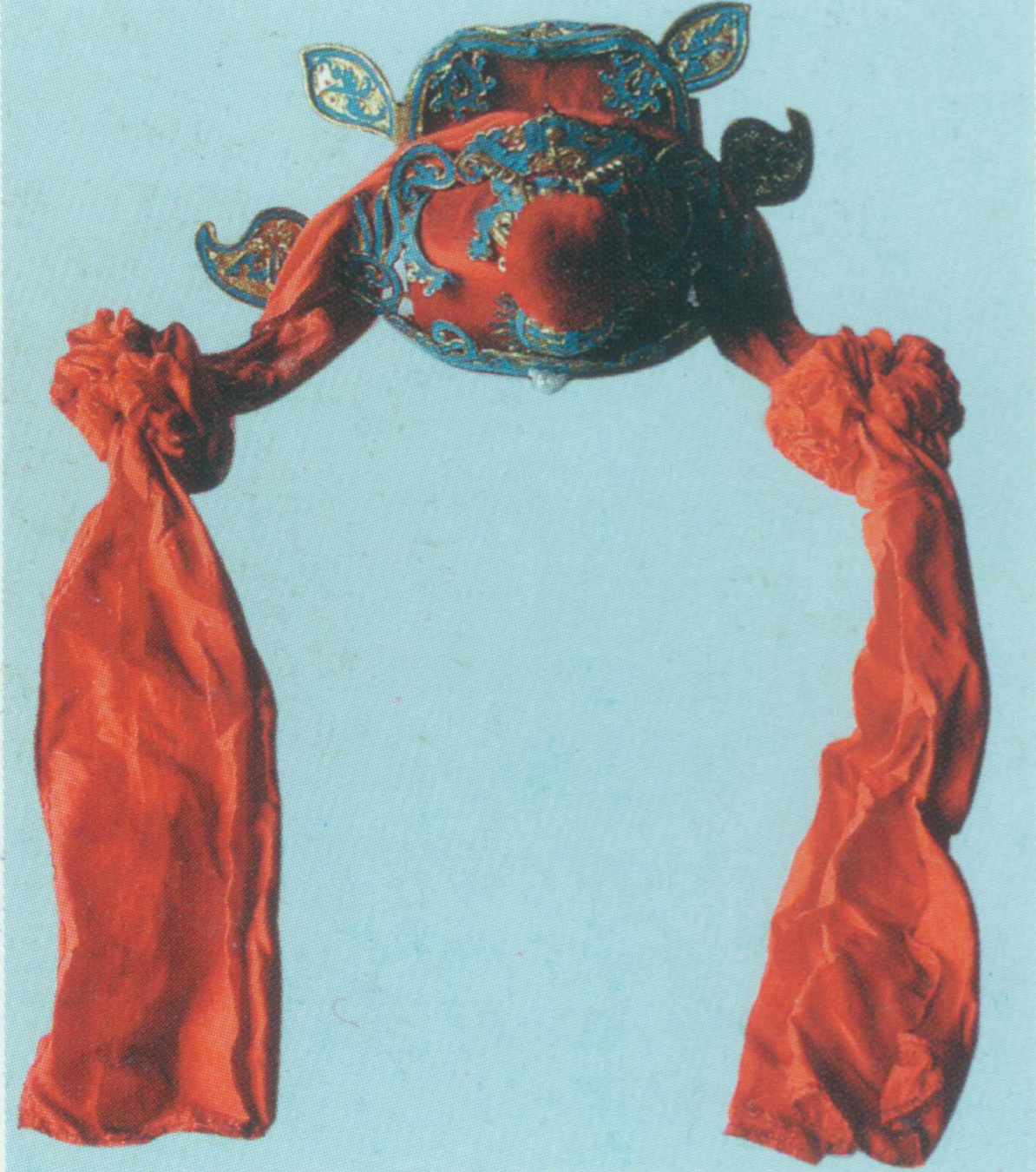 """Judge Hat    A rigid helmet. It resembles square gauze hat in looks. There is a round warped- shou  (a Chinese character meaning longevity) encircled flame at the frontal center and a big red velvet ball atop. It also has a pair of wings pointing upwards is in the behind, with other ornaments such as beads, bats and velvet balls. It is commonly seen in red or black. Only judges and the like in Chinese mythologies wear this hat. For example, Zhong Kui just wears a judge hat in the Act """"The marriage of Zhongkui's younger sister"""" of  Happy Endings for Everyone ."""