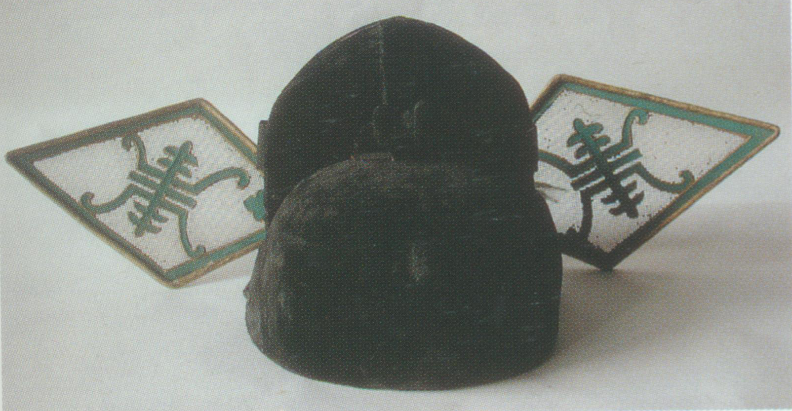 """Pointed Gauze Hat    A rigid helmet. Its full name is """"gauze hat with pointed wings"""" and is also known as """"the treacherous hat"""" because it is usually worn by disloyal officials. It resembles the square gauze hat in shape, except for its pointed wings. """"Pointed"""" and """"treacherous"""" are homophonic in Chinese, hence its two names."""