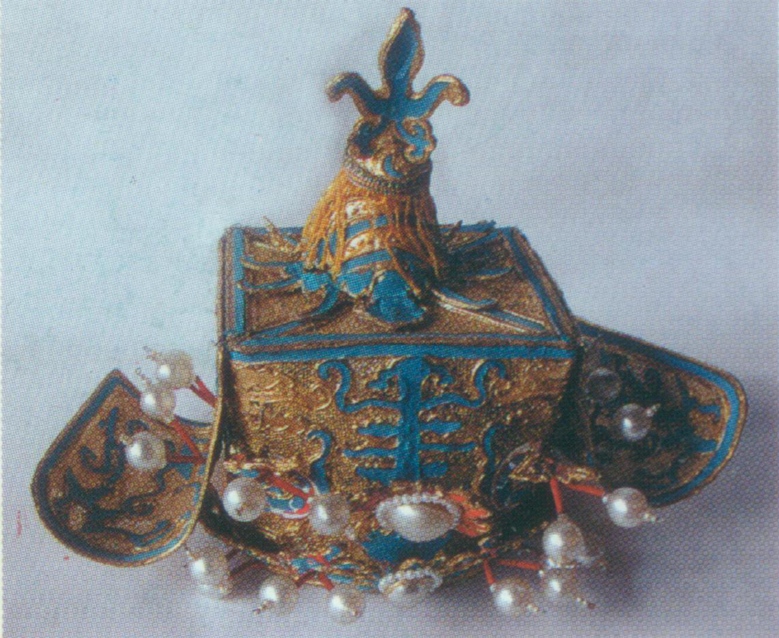 """Marquis Hat   A rigid helmet. It is square-shaped with a flat top. There is a round warped- shou  (a Chinese character meaning longevity) encircled by flames, a big apricot velvet ball, and a pair of slender dragons at the frontal center. A pair of wide wings with bullion fringes is fixed to the hat. Typically, it is worn by people who have been conferred a rank of nobility, i.e. marquis. If the marquis has military power, then his hat should have an additional halberd head atop (called as """" Taiding """"), the same as the one worn by Liang Ji in  Joys of the Fishermen ."""