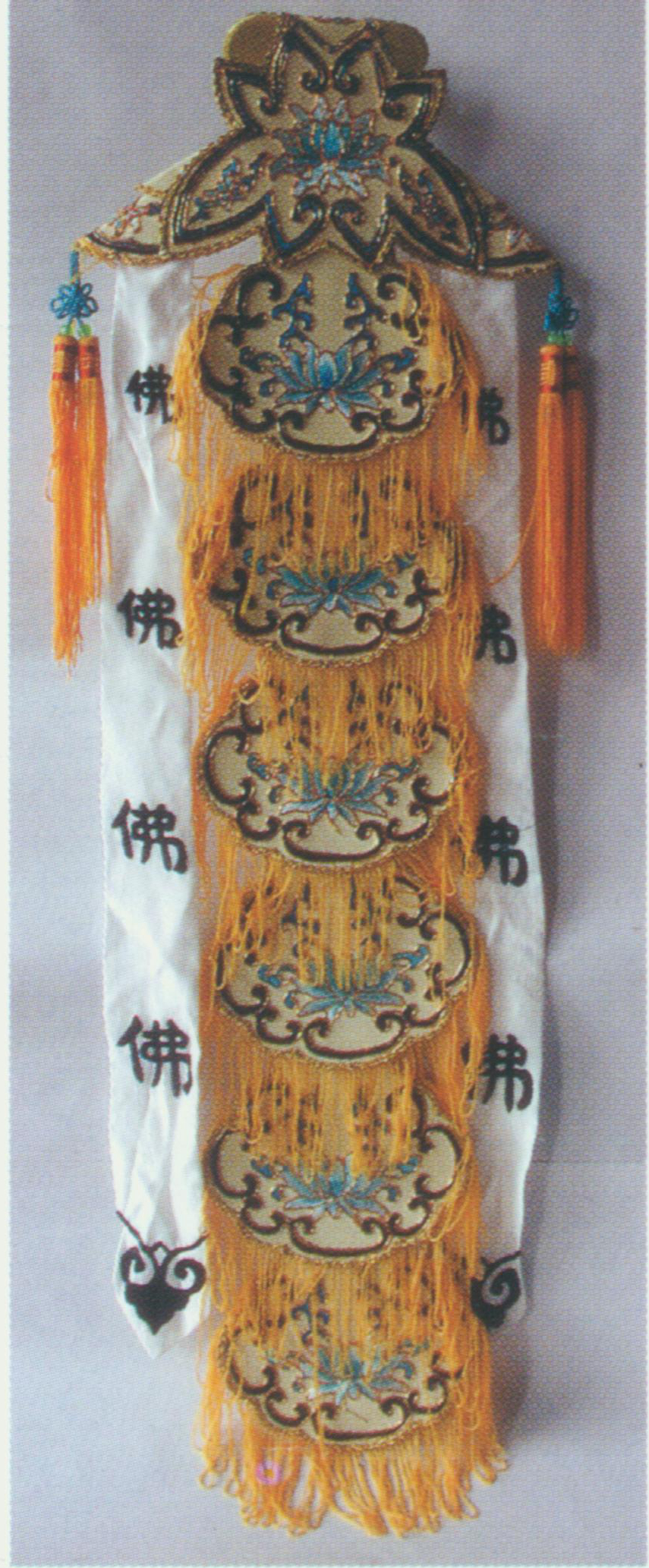 """Taoist Priestess Scarf    A soft hat, also known as """"Miaochang Scarf"""" for it is worn by Chen Miaochang, a character in  The Jade Hairpin . The top is made of two ladder-shaped satin cloths. A pair of ribbons embroidered with the word """"Buddhism"""" in Chinese is attached to the hat on both sides. The back consists of six light yellow or white oval cloths, with the word """"Buddhism"""" in Chinese at the center. The hat is decorated with yellow bullion fringes and two shorter ribbons at bottom. It is worn by Taoist priestess, hence the name."""