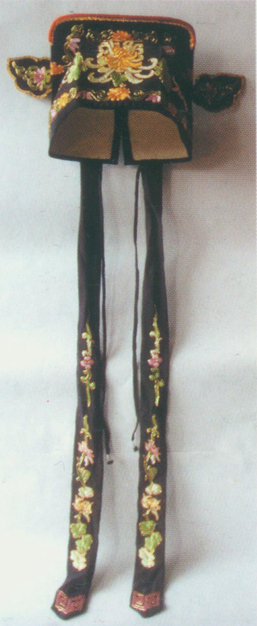 """Zhiliao    Scarf  A soft hat, also known as the """"Stick Scarf"""" (bang zhu jin). This square hat has a pair of autumn-leave-shaped wings pointing upwards and two ribbons on the back. It mainly uses red or green, and go with coloured dresses. Young and middle-aged male characters that belong to the  Chou  (the term for male clown roles in  Kunqu ) wear  Zhiliao  Scarf."""