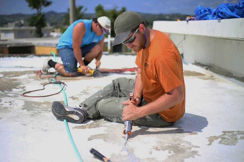 Members Frankie (right) and Eli (left) repair the damaged roof of a homeowner in Puerto Rico. Photo credit: Wyatt Berrier