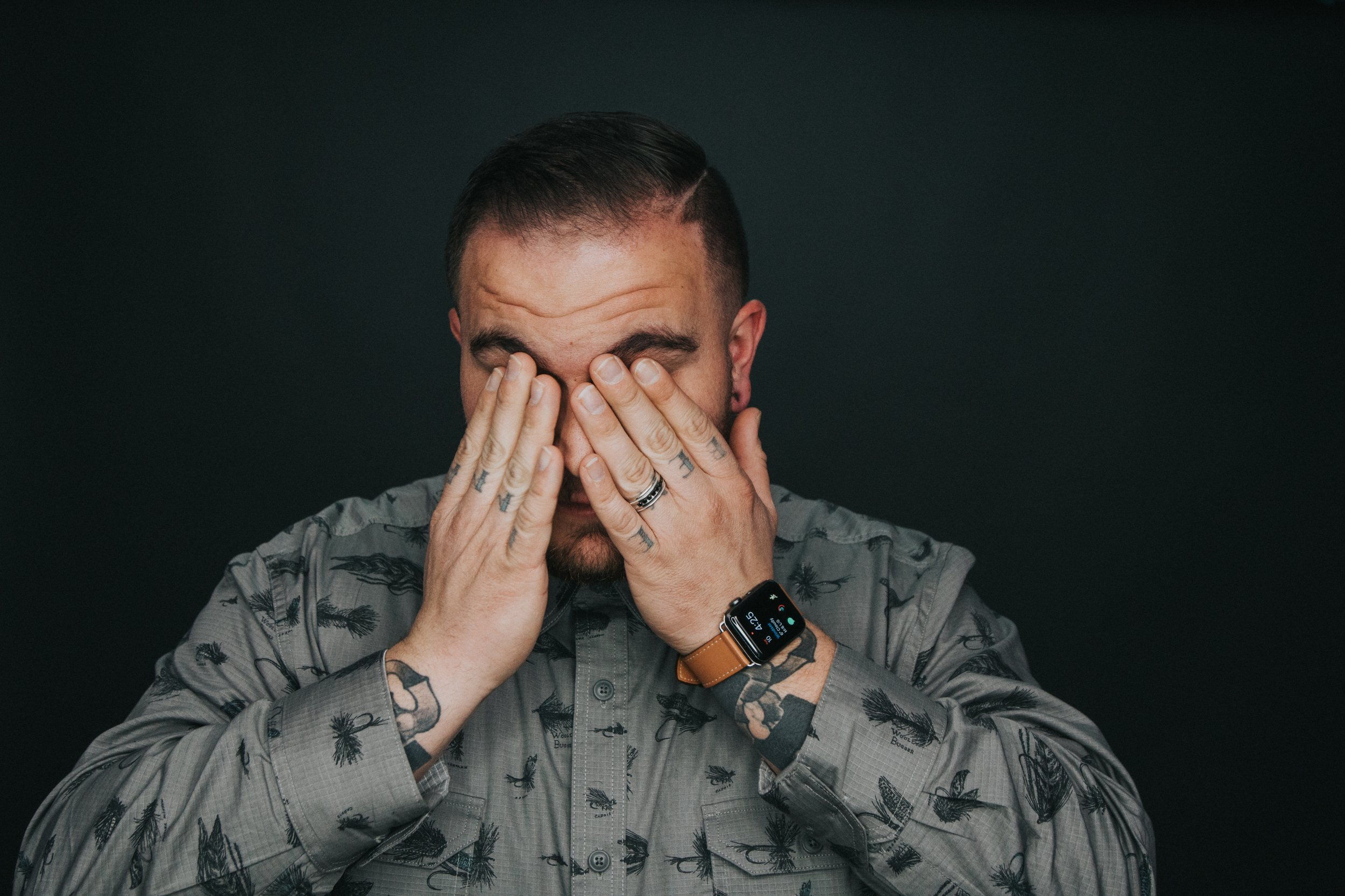 Man with hands covering his eyes