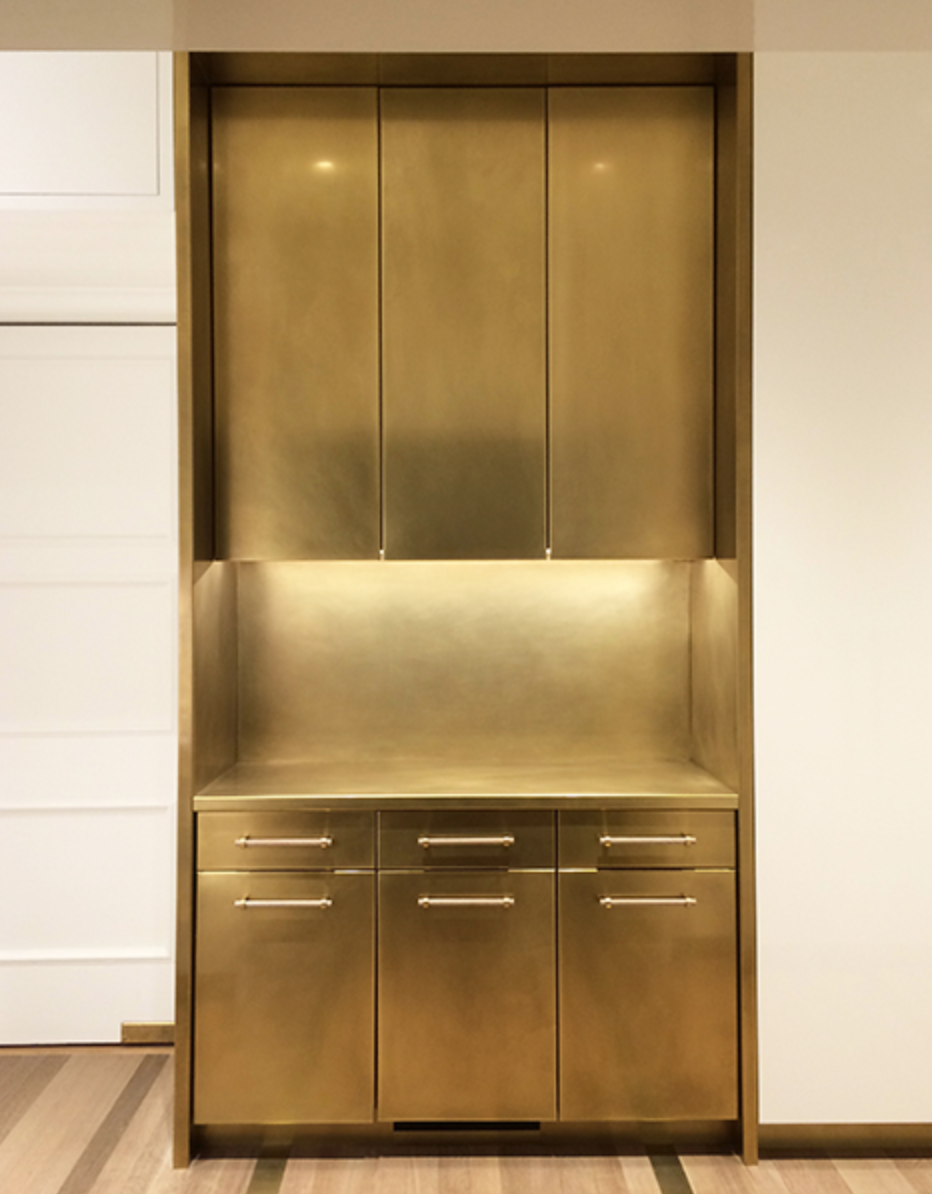 Amuneal installed this brass unit as part of a full kitchen design in a Pennsylvania home. The brass pops against glossy white lacquered cabinets. Photo by Goldenberg Photography