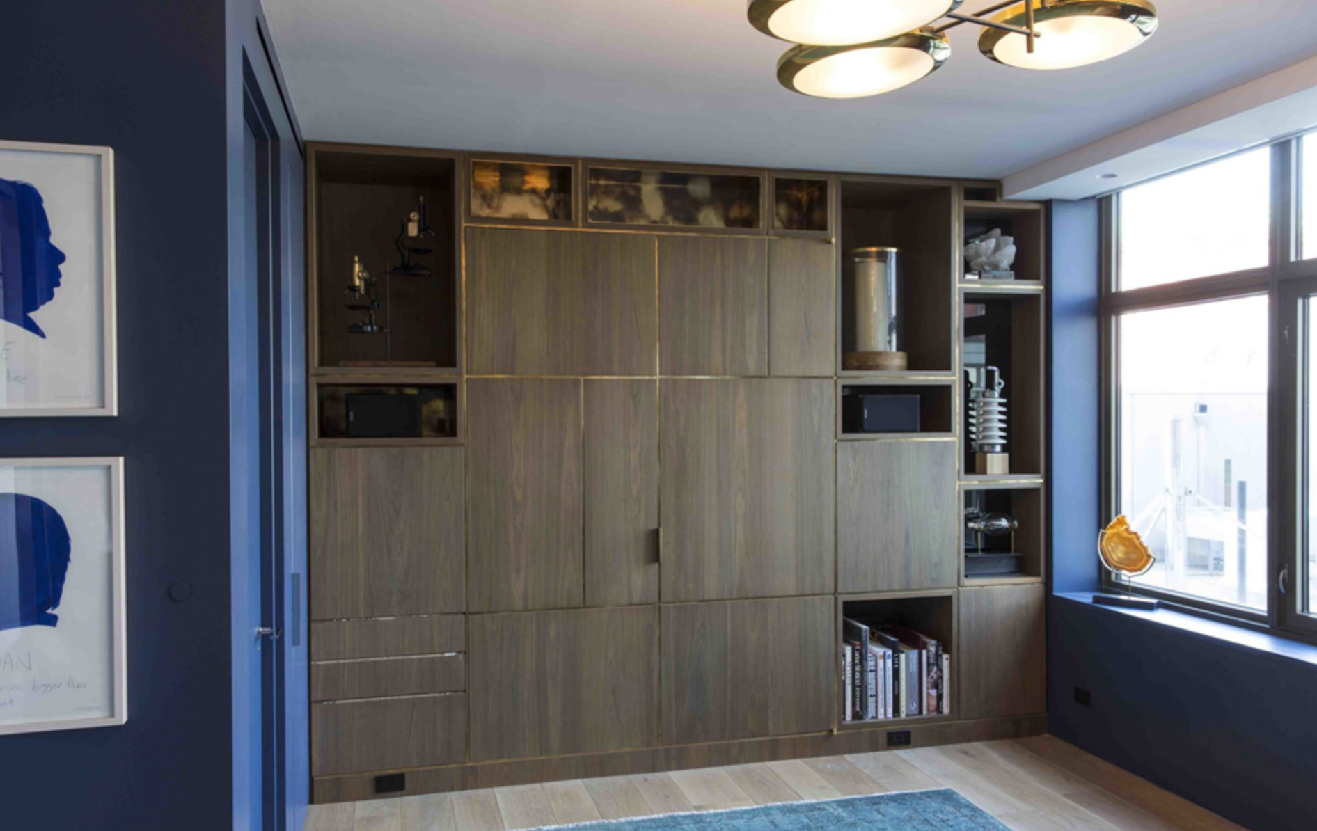 When closed, the Murphy bed in this Manhattan apartment looks like a wall of walnut cabinetry with brass inlays. Photo by Goldenberg Photography