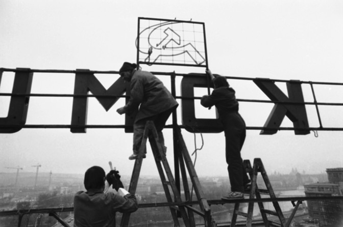 "Workers remove a hammer and sickle from a neon sign that reads ""Glory to Communism,"" visible on the roof of the Communist-run electricity-board headquarters in Czechoslovakia in 1989. (AP)"