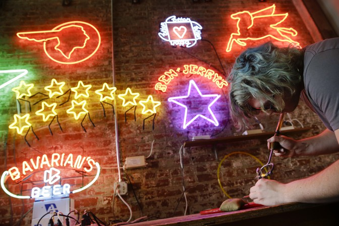 Martin Wartman, a student at Northern Kentucky University, works on a neon sign at the Neonworks of Cincinnati workshop connected to the American Sign Museum, in 2016. (John Minchillo / AP)