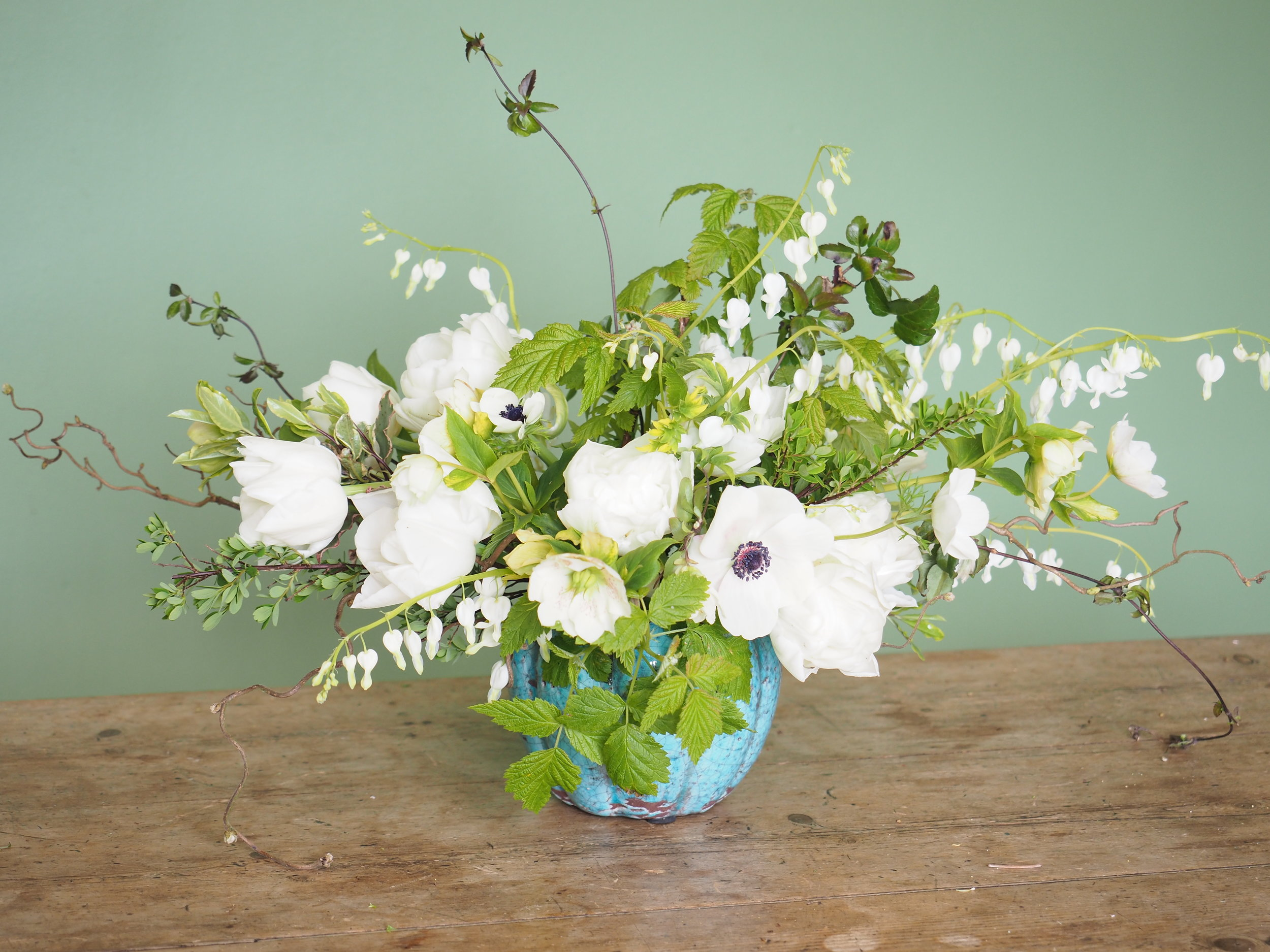 A cutting garden arrangement with 'Mondial', Anemones, hellebores, dicentra and raspberry greens.