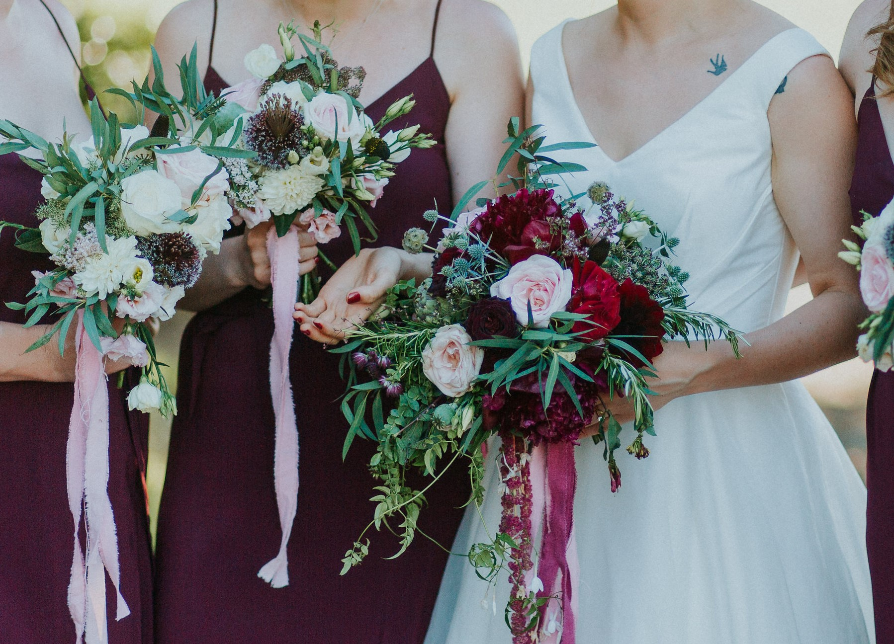 The dark burgundy of these alliums in the bridesmaid's bouquets added a great contrast again the pale flowers. Photo from  Nathan English Photography