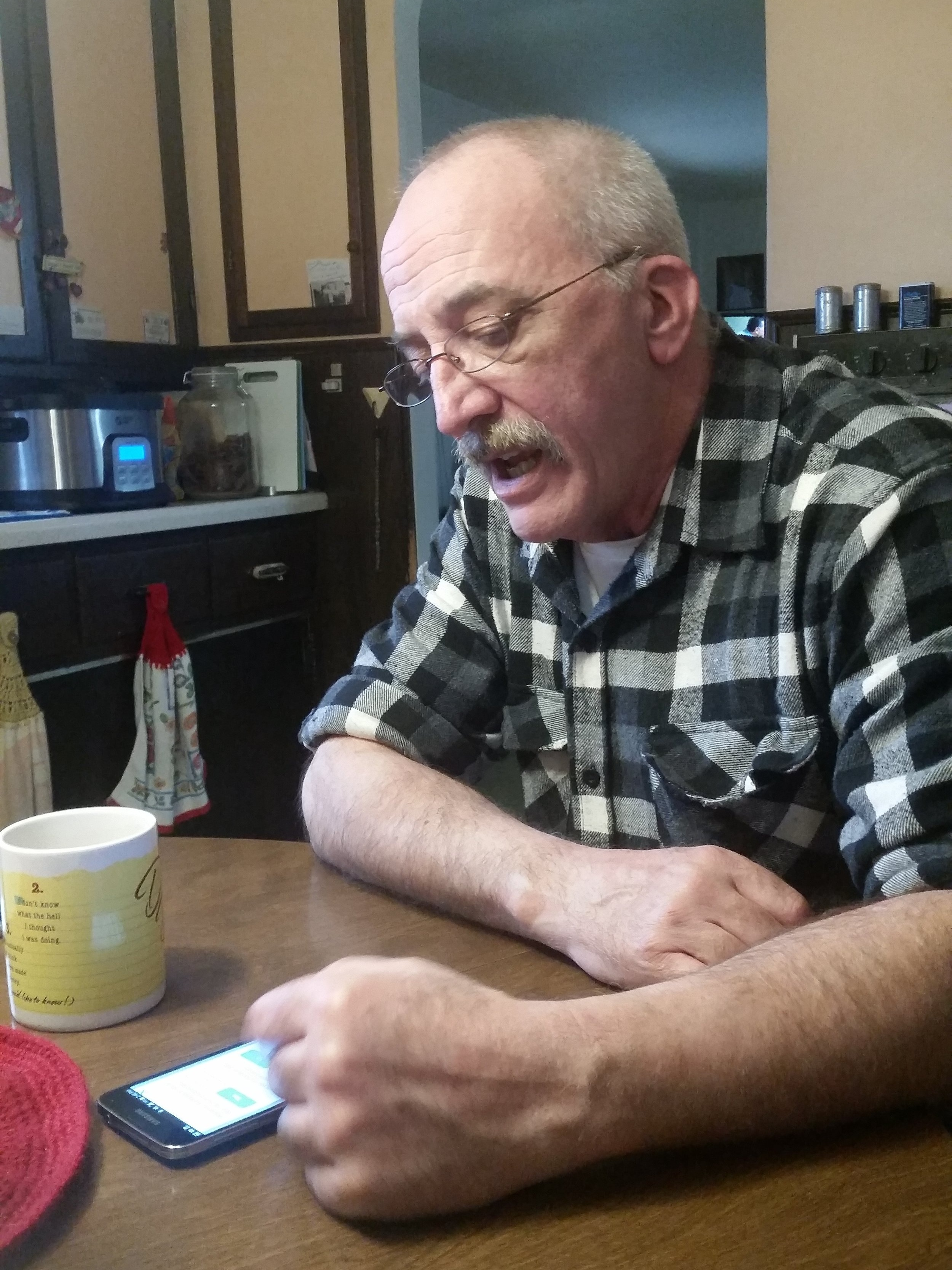 This caregiver takes care of his mother and uses Vela on his phone.