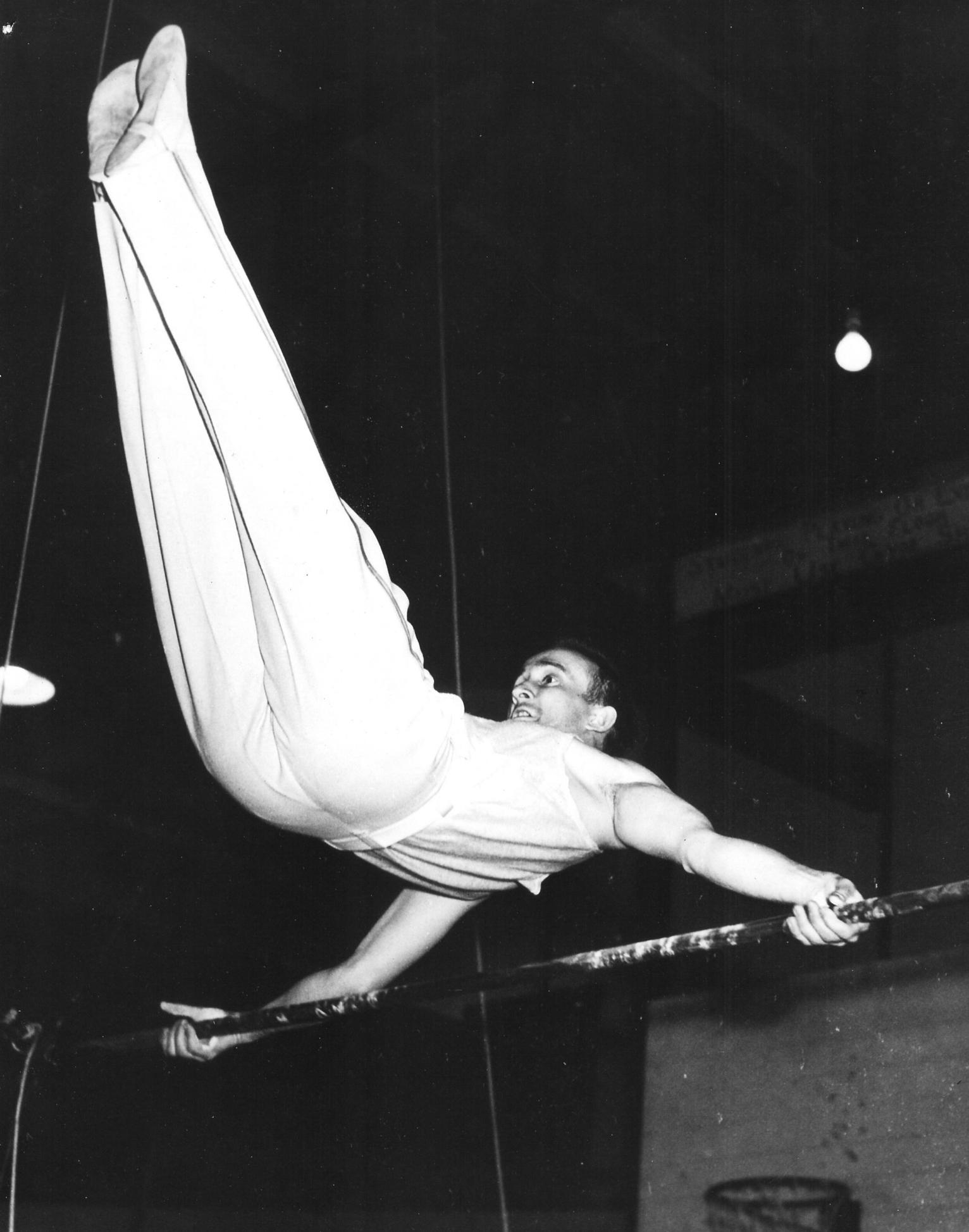 Capt. Charles Pinckney doing an Eagle on the Horizontal Bar (1950)