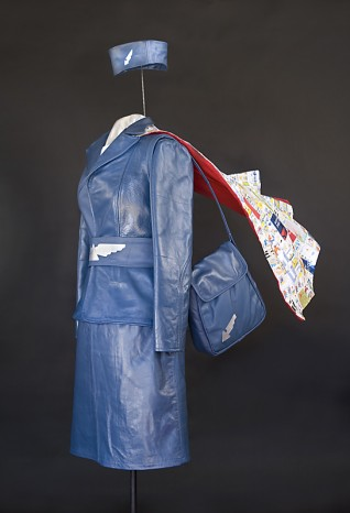© Nancy Judd  The Environmental Stewardess 2011: Commissioned by Delta Airlines, this outfit is made entirely of worn out leather plane seat covers and safety flyers, with a cape of Sky Magazines, old plane tickets and pretzel wrappers sewn onto old pillow cases, and lined with a discarded Delta blankets. The Purse was designed and made by  Tierra Ideas .