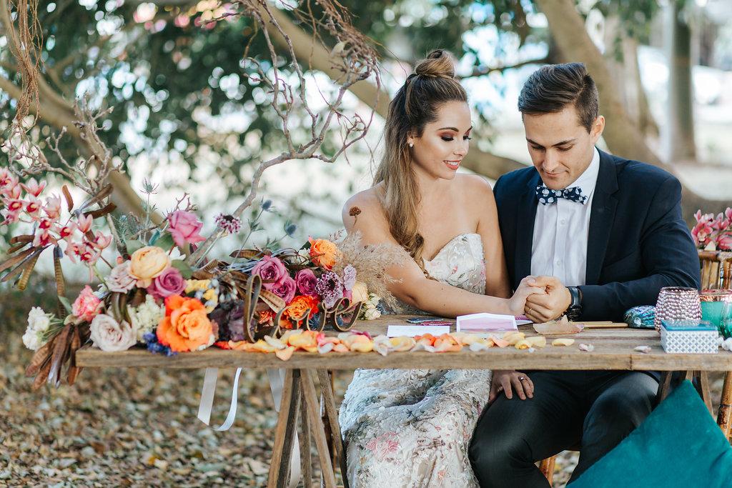 Bloodwood Botanica   Bohemian bright wedding signing table flowers