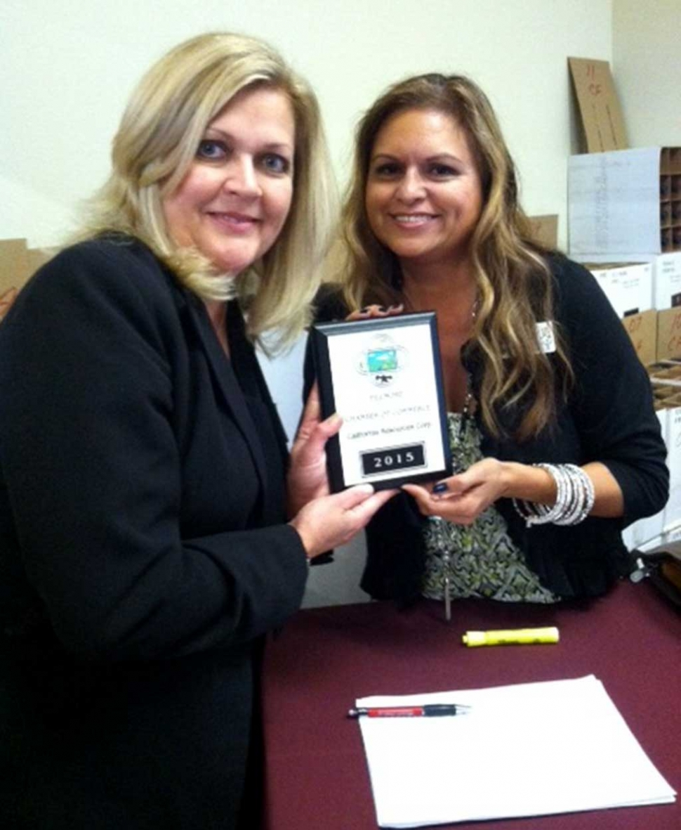 """Fillmore Chamber board member Ari Larson presents a membership plaque to Amy Fonzo from California Resources Corp. CRC is the largest oil and natural gas producer in California on a gross-operated basis. CRC is proud to support the Fillmore community where it operates and producing """"Energy for California by Californians."""""""