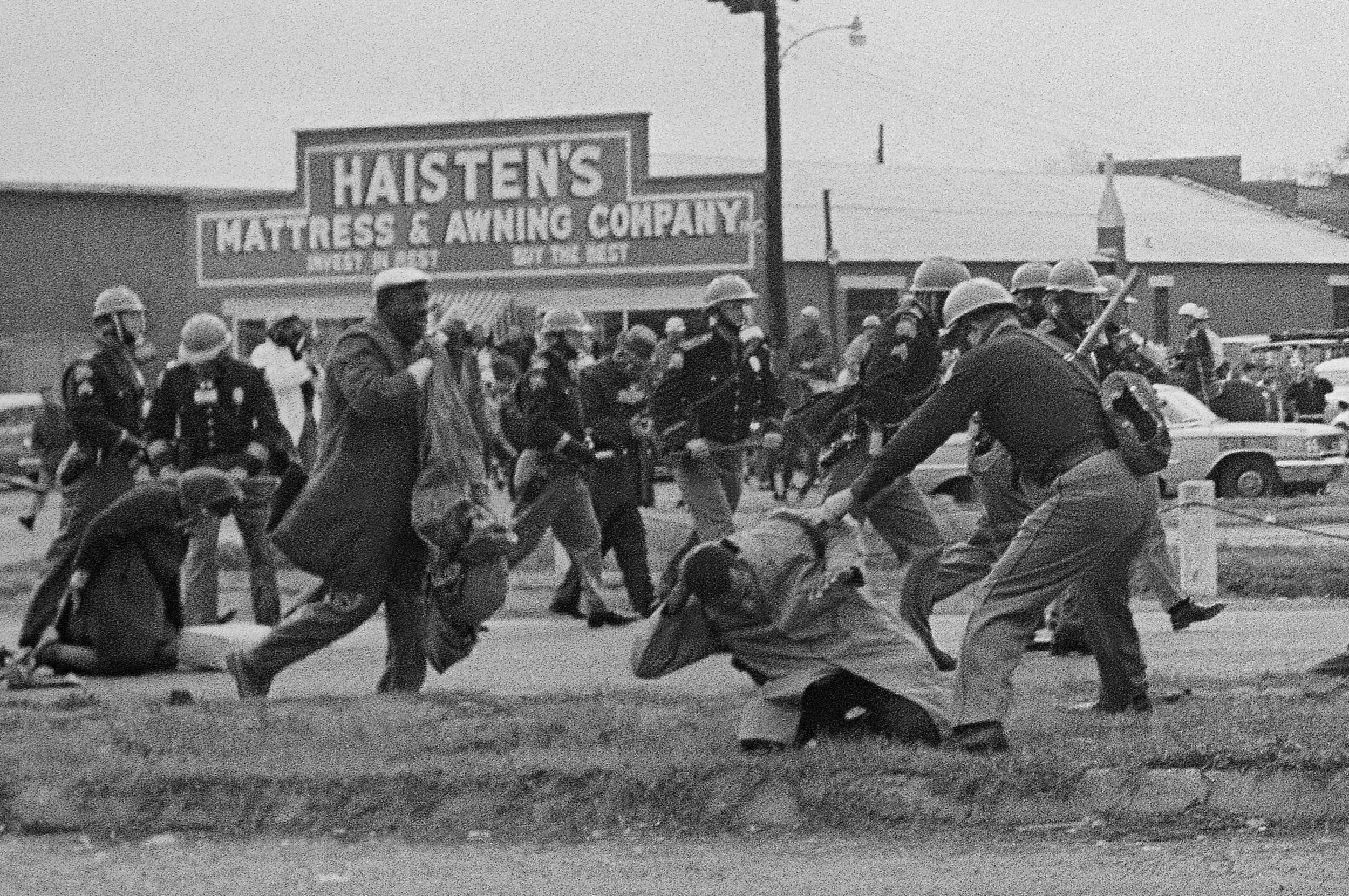 PAGE 92: DURING THE FIRST ATTEMPT TO MARCH FROM SELMA TO MONTGOMERY, SCLC FIELD DIRECTOR HOSEA WILLIAMS AND SNCC CHAIRMAN JOHN LEWIS LED MORE THAN 500 DEMONSTRATORS ACROSS THE EDMOND PETTIS BRIDGE ON MARCH 7, 1965. THE CROWD WAS MET WITH BLOODSHED AS STATE TROOPERS AND POLICE OFFICERS SWUNG BILLY CLUBS AND TRAMPLED AND TEAR GASSED MALE AND FEMALE PROTESTORS. LEWIS IS PICTURED RECEIVING BLOWS TO THE HEAD AND BODY (PERMISSION OF THE ASSOCIATED PRESS).