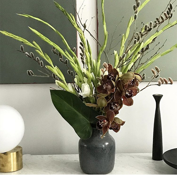 Focal point arrangements are often a mix of long lasting flowers. Here we have cymbidium orchids, gladiolus, and pussy willow.