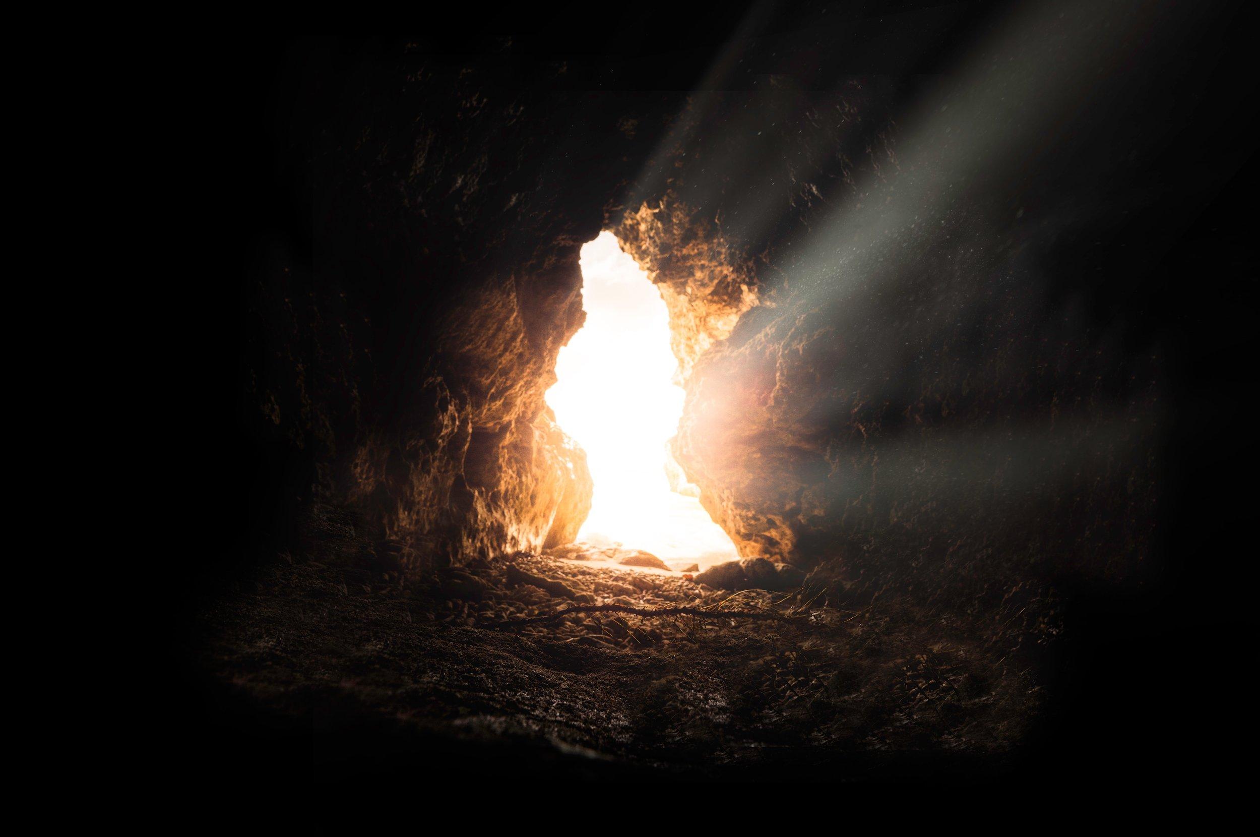 A photograph of light shining through a cave entrance