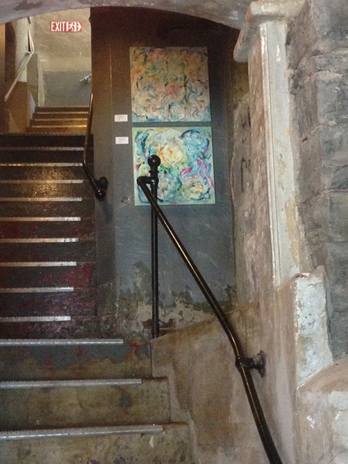 View of the stairs from one level to another with 2 of my paintings.