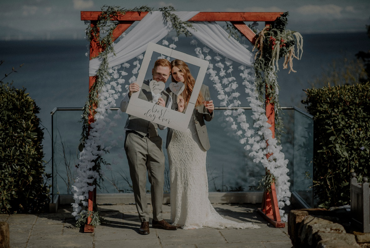 bride and groom are posing to the camera