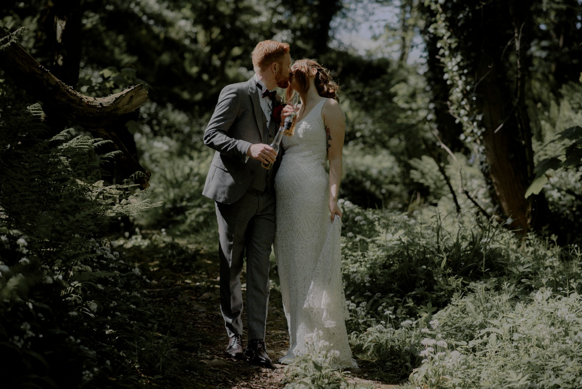 couple is kissing whilst holding bottle of beer