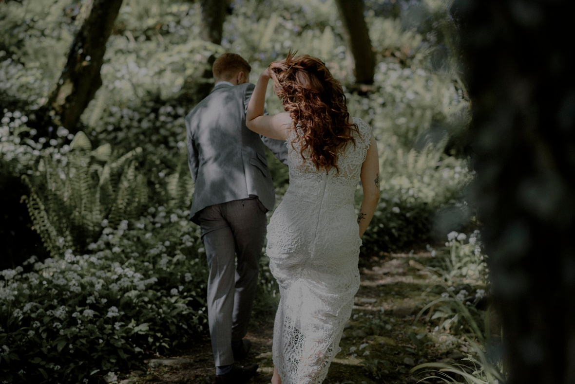 bride and groom are walking in forest