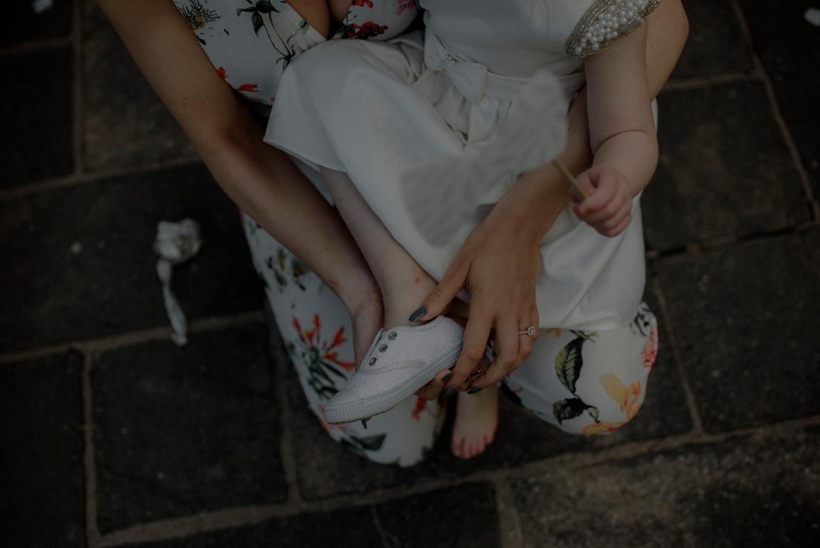 little girl is putting shoe on