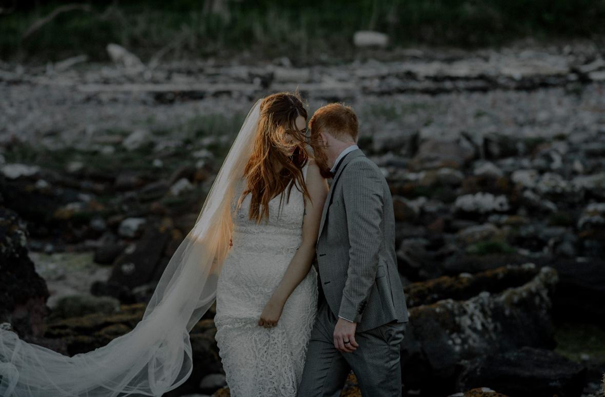 groom is kissing bride's shoulder