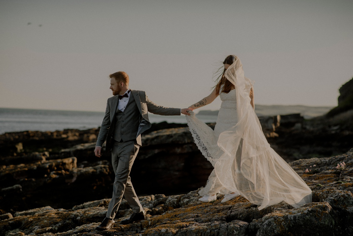 bride and groom are walking on beach