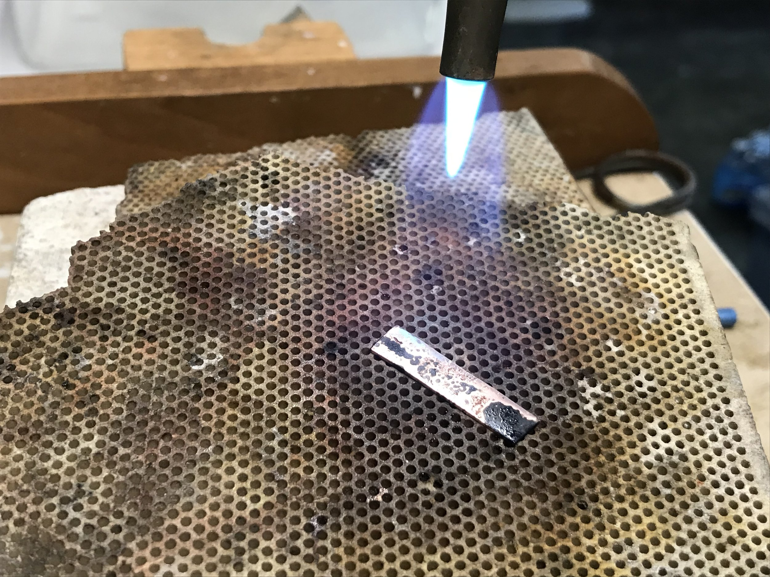 Step 2. - Anneal the brass strips and copper washers by heating them with a torch. Annealing makes the metal soft and pliable.