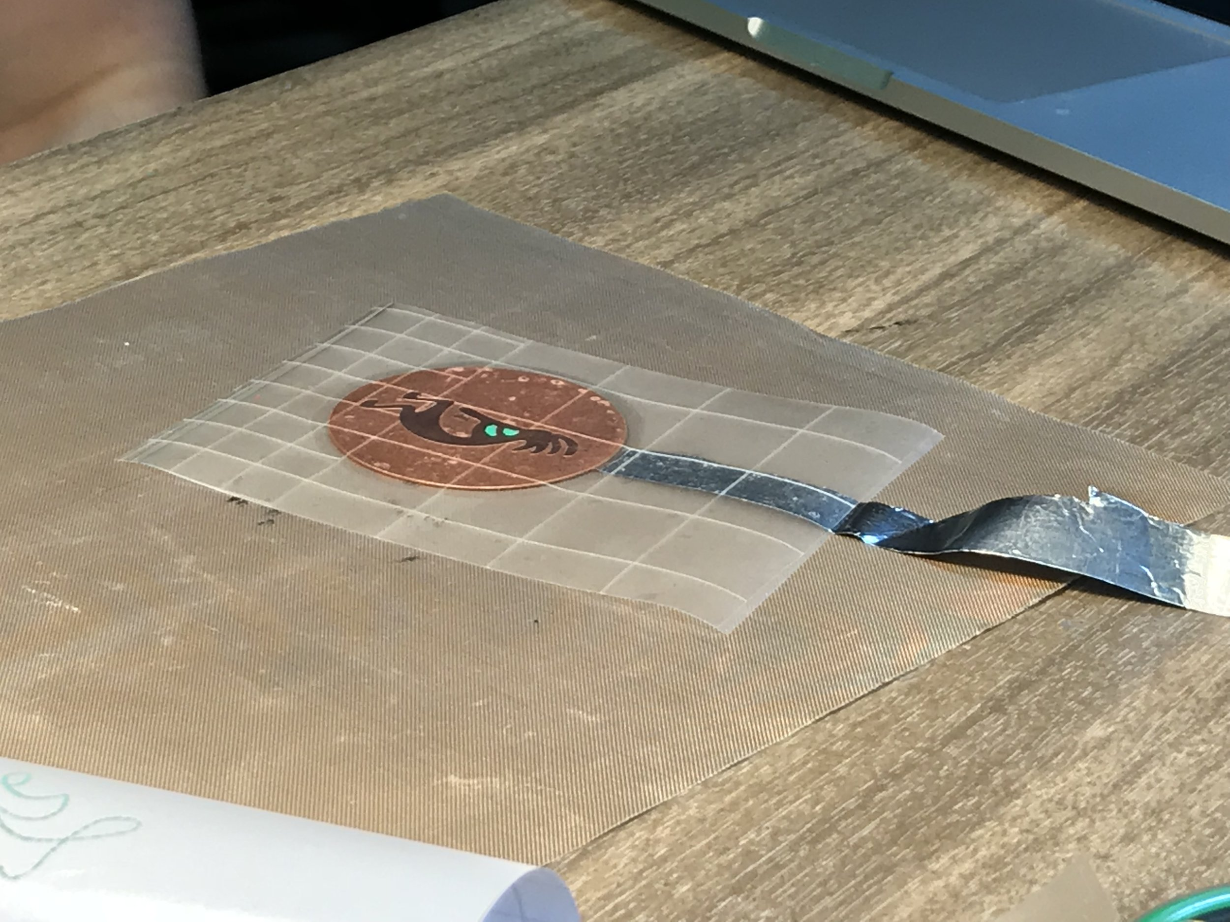 """- 3. Stick a strip of aluminum foil to the metal to be etched using squares of """"Contact Paper""""."""