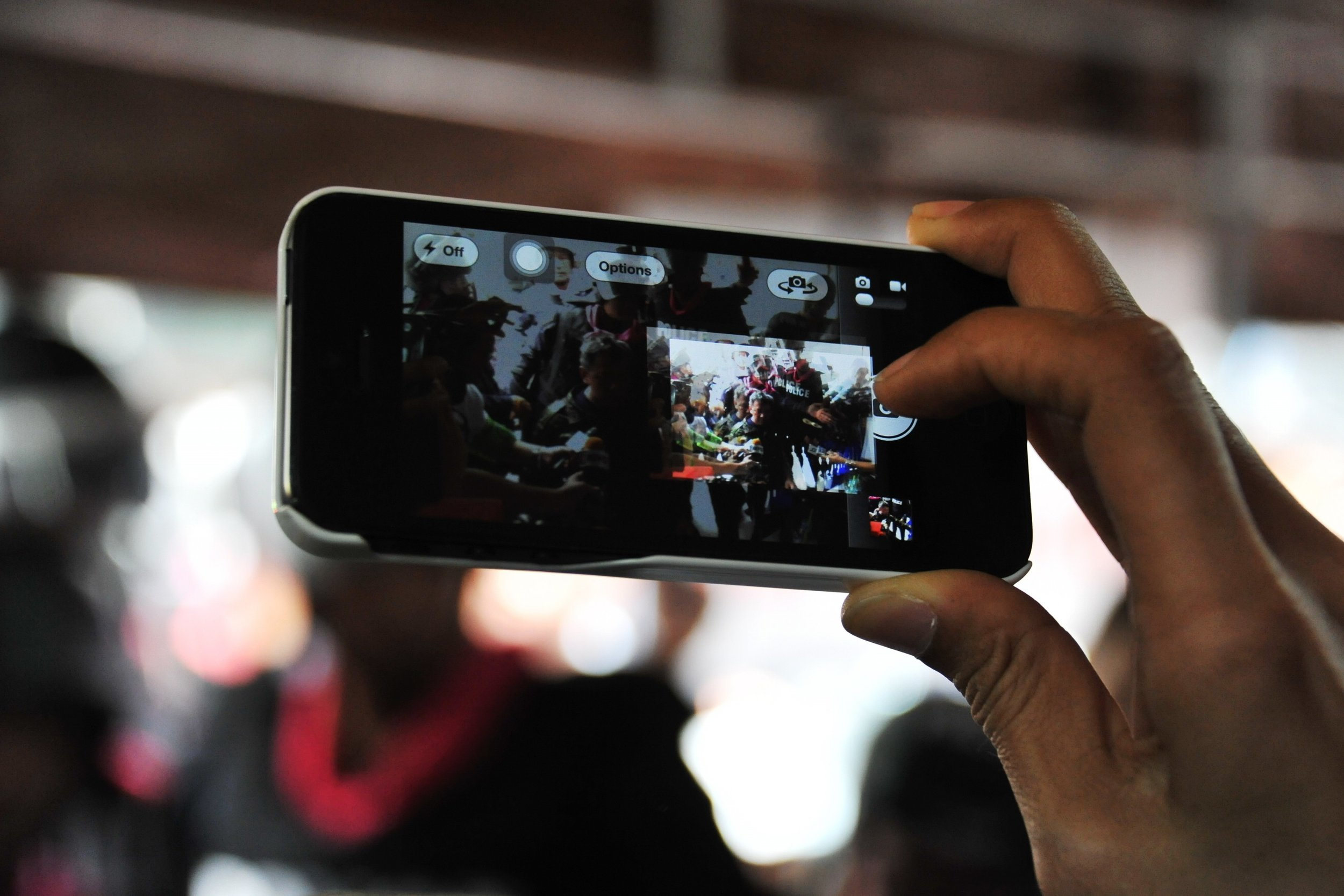 A close up shot on a hand holding a cell phone as the owner films police officers.