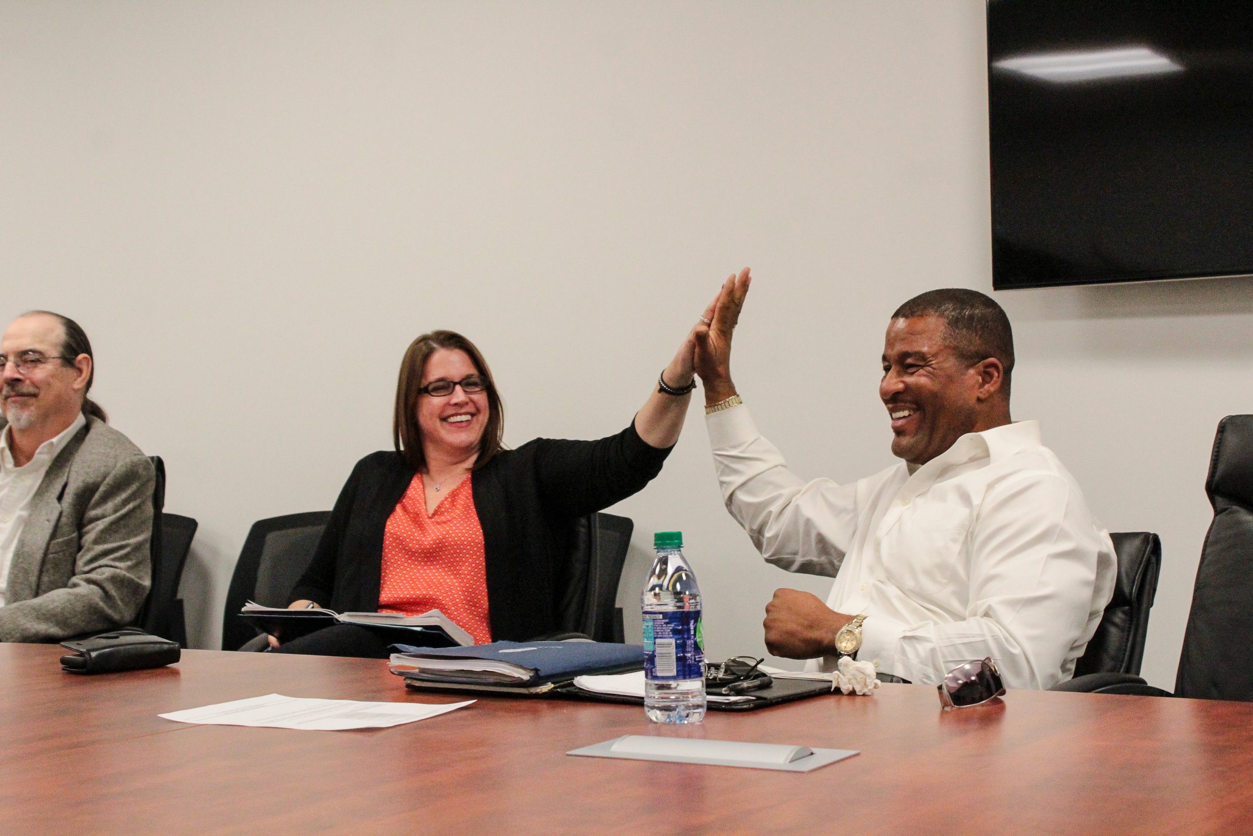 Jennifer Zeunik of the National Police Foundation high-fives Policy Committee member Darius Williamson.