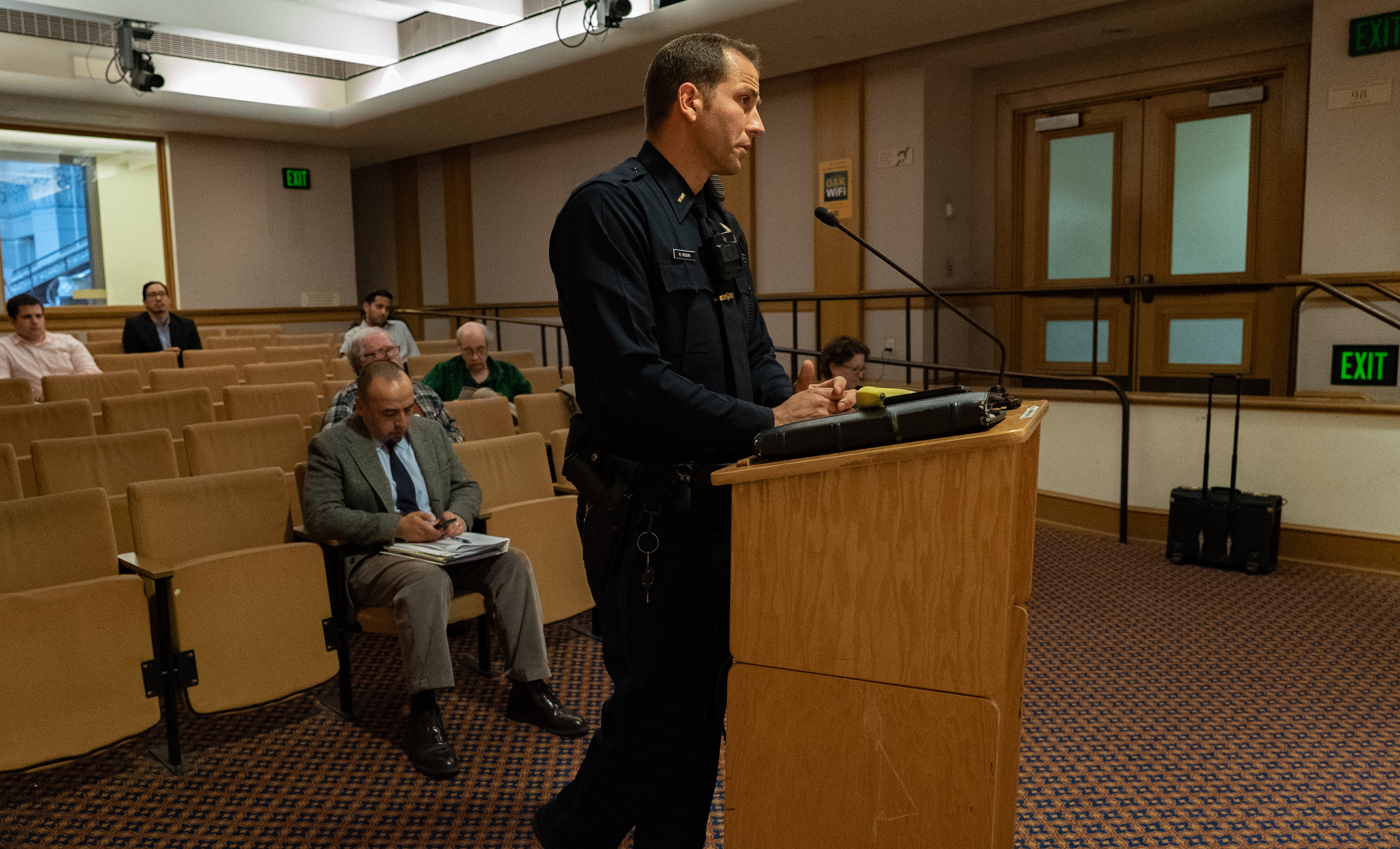 An Oakland Police Department officer speaks on the benefits of automated license plate readers before the Commission.