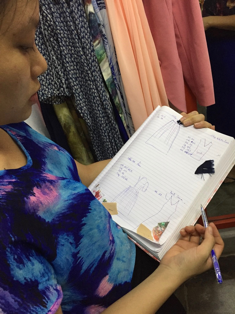 Anna's fashion partner designing clothes in Hoi An