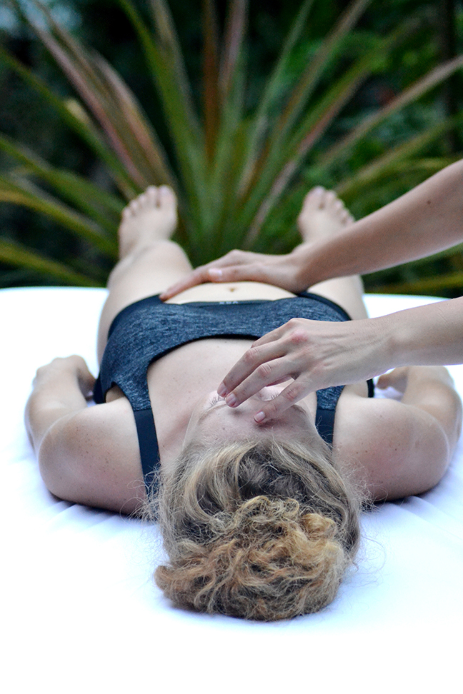 Woman lying down. Osteopath hands on face and abdomen.