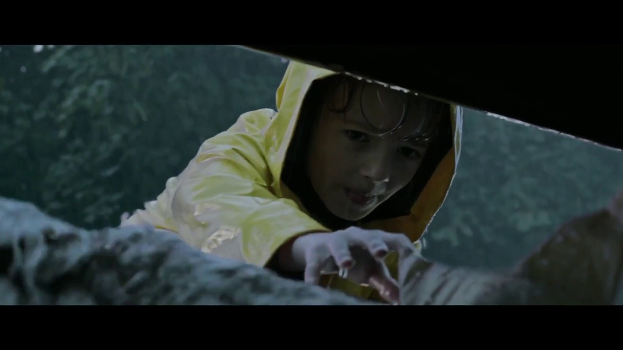 Jackson Robert Scott, as Georgie Denbrough, reaches into the sewer to retrieve his paper boat from Pennywise the Dancing Clown in  It