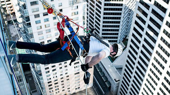 Pic of someone abseiling down 33-story building face first for Abseil For Youth!