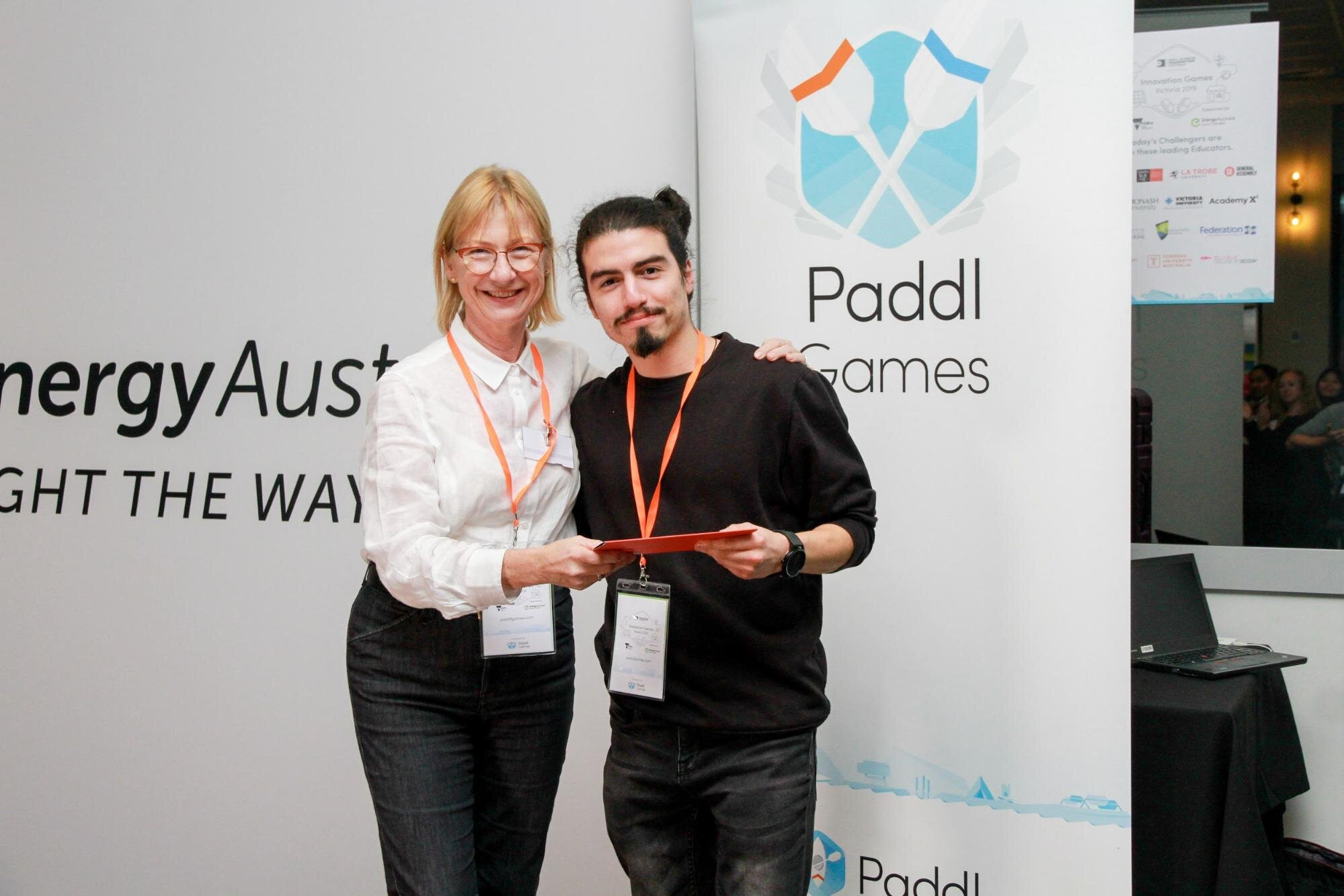 Daniel receiving his prize from and Dominique Fisher, Paddl Co. CEO and Top XP Profile at Paddl!