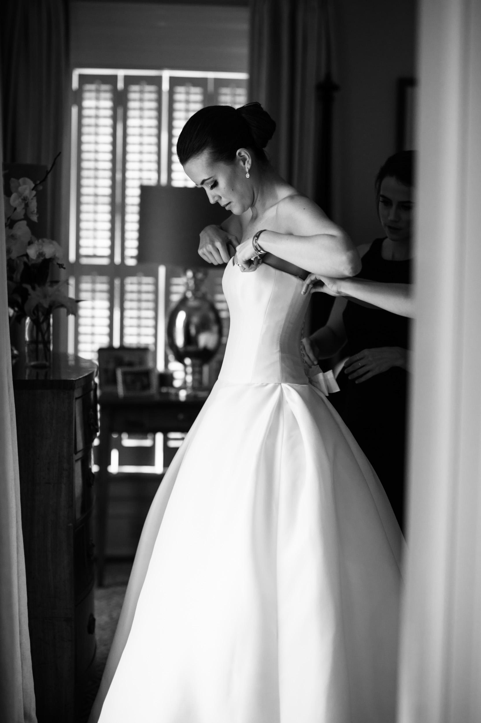 sisters helping bride zip wedding dress