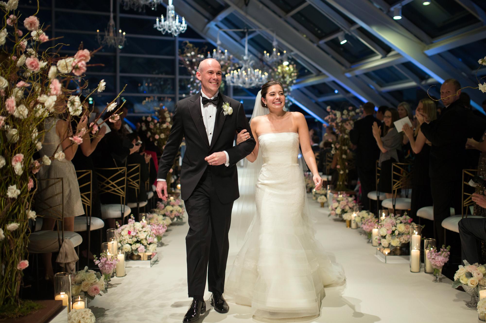Bride and groom exit wedding ceremony at Adler Planetarium in Chicago.