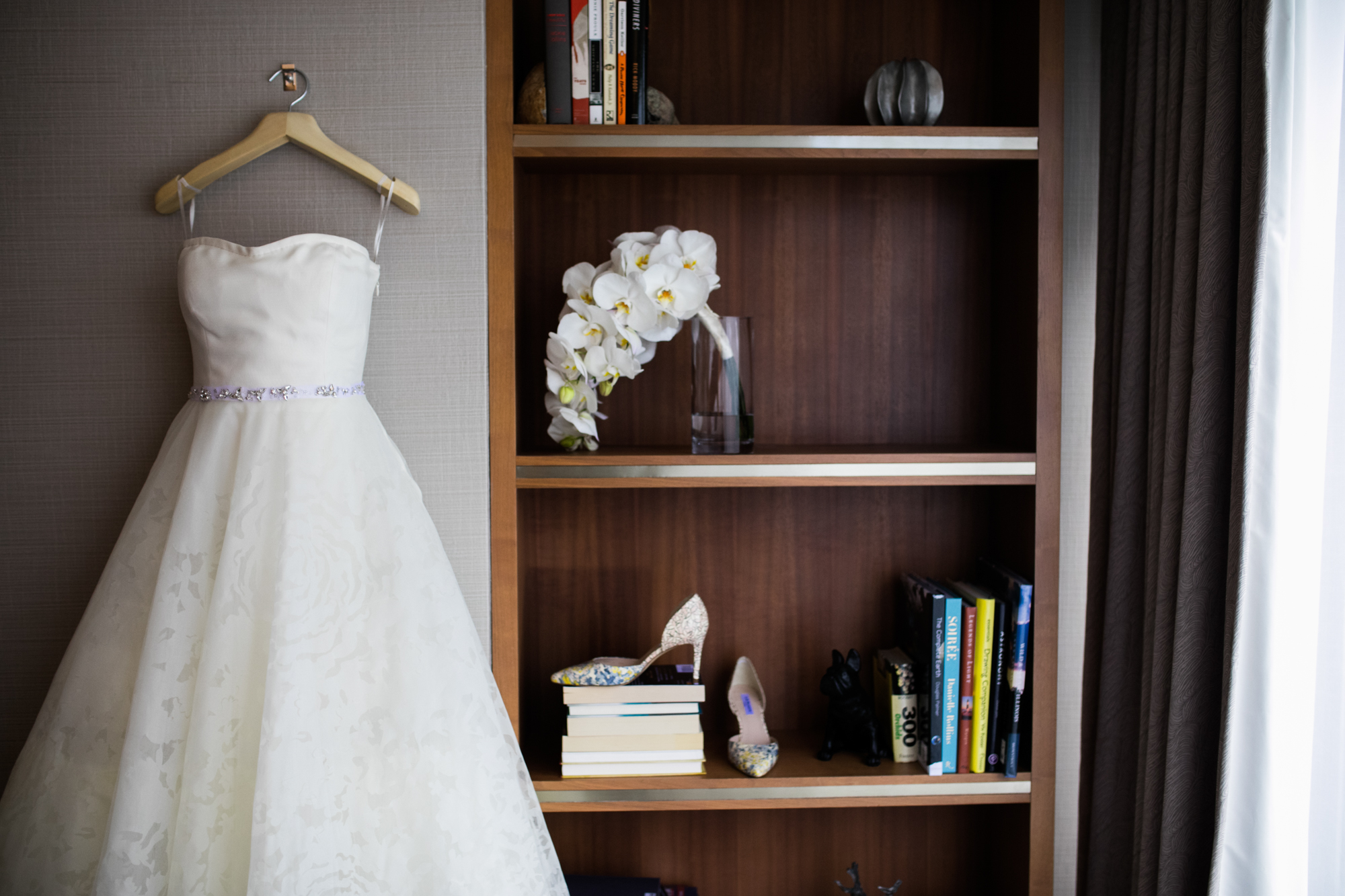 A bride's gown, shoes, and orchid bouquet for her wedding at Millennium Park Harris Rooftop in Chicago, Illinois.