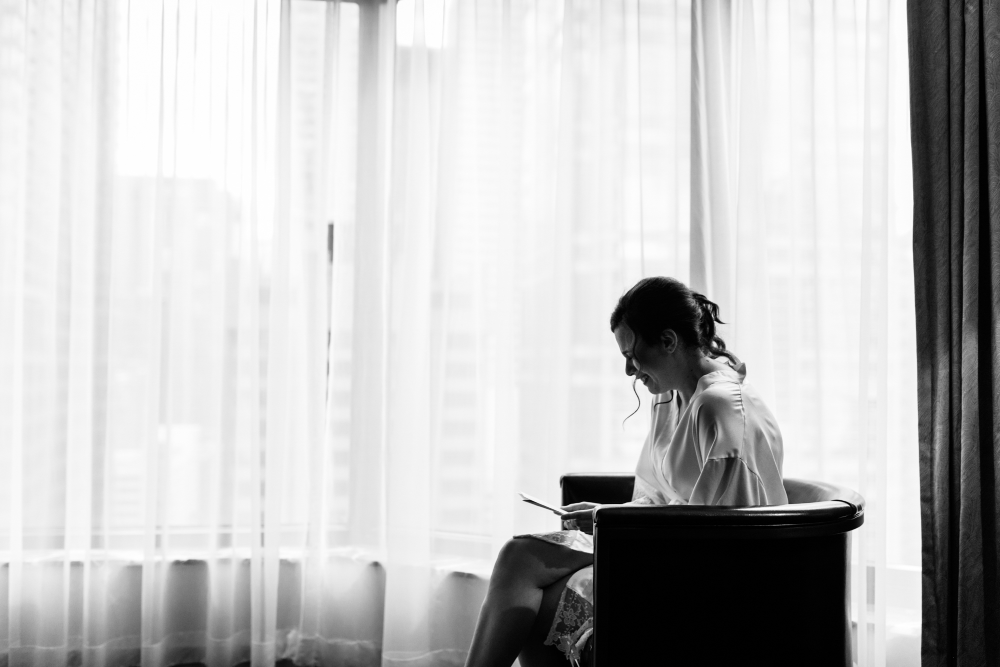 Candid photo of a bride reading a letter on her wedding day in Chicago.