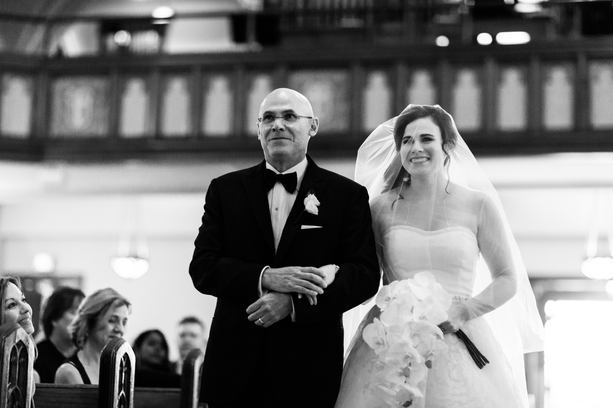 Bride and her father walk down the aisle during wedding ceremony at St James Lutheran Church in Chicago.
